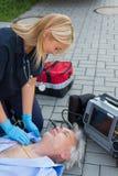 Paramedic examining unconscious elderly man Stock Images