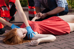 Paramedic helping unconscious woman. Horizontal view of paramedic helping unconscious woman Stock Photos