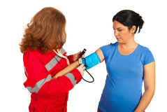 Paramedic measure blood pressure to woman Stock Image