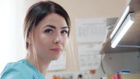The paramedic nurse on duty looked briefly at the camera lens. The duty paramedic nurse of good looks, a brunette, in a special uniform, at her desk performs stock footage