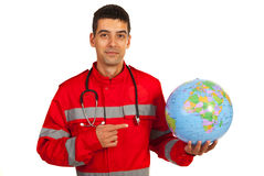 Paramedic pointing to earth globe Royalty Free Stock Photo