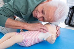 Paramedic practicing resuscitation on dummy. In clinic Royalty Free Stock Photography
