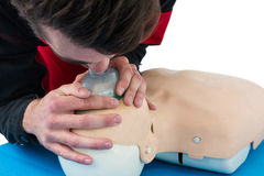 Paramedic practising resuscitation mouth to mouth on dummy Stock Photo