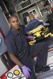Paramedic preparing to unload patient Stock Photo