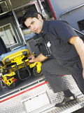 Paramedic removing gurney from ambulance Stock Photography