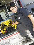 Paramedic removing gurney from ambulance Stock Photography