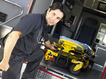 Paramedic removing gurney from ambulance Royalty Free Stock Photo