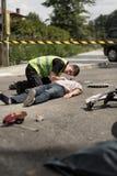 Paramedic resuscitating traffic collision victim. Photo of paramedic resuscitating injured traffic collision victim Stock Photo