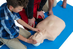 Paramedic training cardiopulmonary resuscitation to boy royalty free stock image