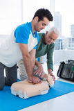 Paramedic training cardiopulmonary resuscitation to man. Paramedic training cardiopulmonary resuscitation to men in clinic stock images
