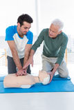 Paramedic training cardiopulmonary resuscitation to man. Paramedic training cardiopulmonary resuscitation to men in clinic royalty free stock image