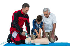 Paramedic training cardiopulmonary resuscitation to senior man and boy royalty free stock image