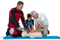 Paramedic training cardiopulmonary resuscitation to senior man and boy stock photo