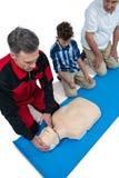 Paramedic training cardiopulmonary resuscitation to senior man and boy royalty free stock photography