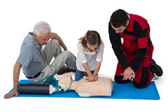 Paramedic training cardiopulmonary resuscitation to senior man and girl Royalty Free Stock Photo