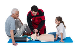 Paramedic training cardiopulmonary resuscitation to senior man and girl Stock Photography