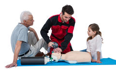 Paramedic training cardiopulmonary resuscitation to senior man and girl Royalty Free Stock Photography