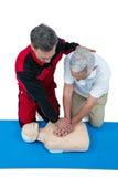 Paramedic training cardiopulmonary resuscitation to senior man royalty free stock photography