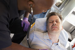 Paramedic using stethoscope on patient Stock Photo