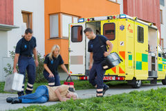 Paramedical team arriving to unconscious elderly man Stock Photography