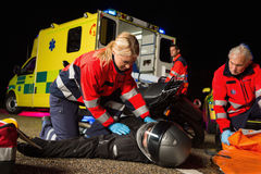 Paramedical team assisting injured motorbike driver Royalty Free Stock Images