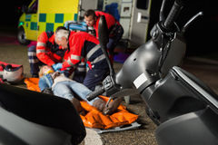 Paramedical team helping injured motorbike driver Stock Images