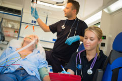 Paramedical team treating man in ambulance car Stock Photography