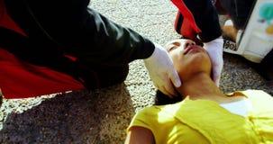 Paramedici che esaminano ragazza danneggiata archivi video
