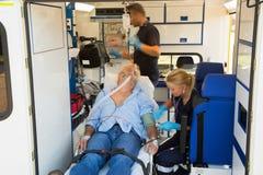 Paramedici die de onbewuste mens in ziekenwagen behandelen Stock Afbeeldingen