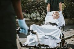 Paramedici die een jonge patiënt op een brancard verplaatsen naar een ziekenwagen stock fotografie
