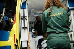 Paramedici die een jonge patiënt op een ziekenwagenbrancard rollen stock foto