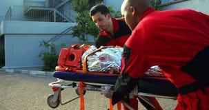 Paramedici die een patiënt in noodsituatie meeslepen stock video