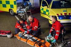 Paramedici die motorbestuurder op brancard helpen Royalty-vrije Stock Afbeeldingen