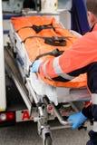 Paramedicinsk rullande ut gurney från den nöd- lastbilen Arkivbild