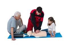 Paramedico che prepara rianimazione cardiopolmonare all'uomo senior ed alla ragazza Immagini Stock