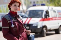 Paramedico femminile positivo con la borsa dell'ambulanza Immagini Stock