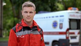 Paramedico maschio che posa per la macchina fotografica, ambulanza su fondo, professionalità fotografie stock