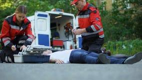 Paramedics που βοηθά το αναίσθητο άτομο που βρίσκεται στο δρόμο, που κάνει την έγχυση με την ινσουλίνη απόθεμα βίντεο