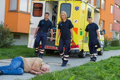 Paramedics arriving to unconscious man. Paramedic team arriving to unconscious senior men lying on street Stock Images