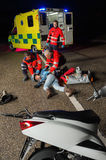 Paramedics assisting injured motorbike driver Royalty Free Stock Photos