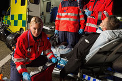 Paramedics assisting injured motorcycle man driver Royalty Free Stock Image
