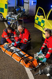 Paramedics assisting motorbike driver on stretcher Stock Image