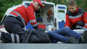 Paramedics caring for man suffering from chest pain, qualified medical care. Stock footage stock video footage