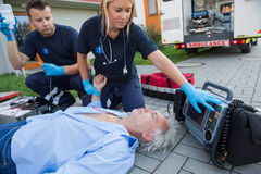 Paramedics checking pulse of unconscious man. Paramedics checking pulse of unconscious senior men lying on street Stock Photo