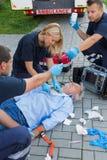 Paramedics examining unconscious man Royalty Free Stock Image