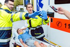 Paramedics fighting people trying to make photos of accident Royalty Free Stock Images