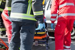 Paramedics and firefighters in urgent rescue operation after a car crash. Paramedics and firefighters in a rescue operation after road traffic accident stock images