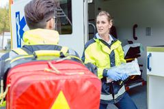 Paramedics in front of ambulance discussing deployment Royalty Free Stock Image