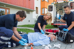 Paramedics giving firstaid to unconscious patient. Paramedics giving firstaid to unconscious senior patient lying on ground Royalty Free Stock Images