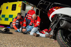 Paramedics helping injured motorcycle driver Stock Images